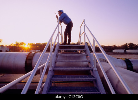 Engineer on a walkie talkie radio at sunset at a waste water treatment plant, Houston, Texas, USA - Stock Image