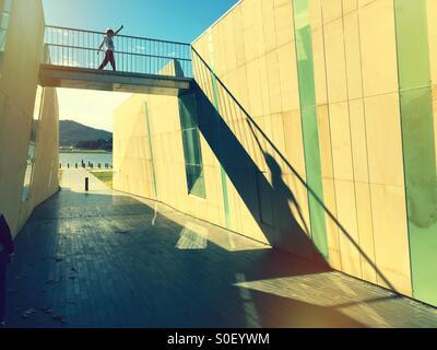 A boy striding across a bridge over an underpass - Stock Image