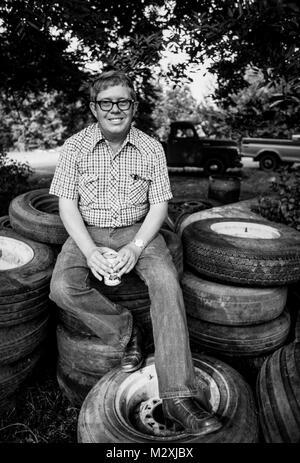 Billy Carter est assis sur une pile de vieux pneus à sa station-service. Il était un agriculteur américain et homme d'affaires et le plus jeune - Image