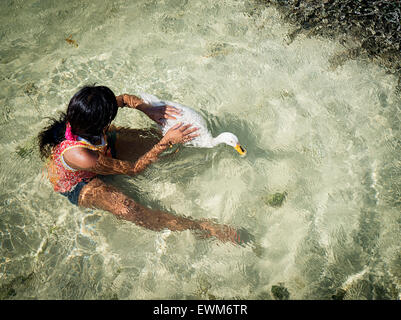 A girl playing with her pet duck in Belize. - Stock Image