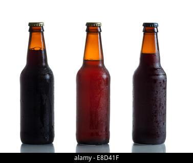 Bouteilles de bière sombres et ambre froides non ouvertes sur blanc avec reflet - Image