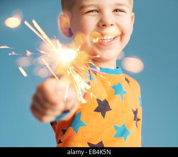 Little man holding a sparkler - Stock Image