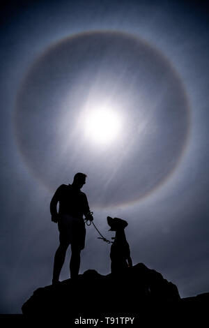 Aberystwyth Wales UK, Thursday 16 May 2019  UK Weather: A man and his dog arr silhouetted as perfect circular sun halo , formed as the rays of the sun shine through ice crystals in the upper atmosphere,  fills the sky above Aberystwyth. The halos, always at 22º from the sun,  often  indicate that rain will fall within the next 24 hours, since the cirrostratus clouds that cause them can signify an approaching frontal system. The  weather is set to change overnight from the fine warm conditions to cooler and wetter days, more typical of mid May.  photo credit Keith Morris / Alamy Live News - Stock Image