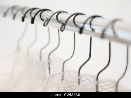 Coat hangers on clothes rack - Stock Image