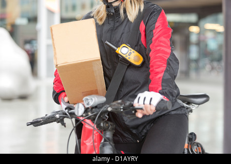 Female Cyclist With Cardboard Box And Courier Bag On Street - Stock Image