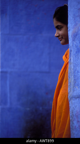 Young women wearing orange Sari stands between blue walls Jodhpur Rajasthan India - Stock Image