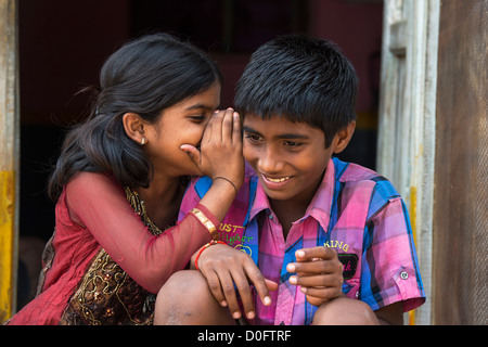 Young Indian girl whispering to a boy outside their rural Indian viilage home. Andhra Pradesh, India - Stock Image