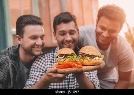 Trois hommes souriants regardant des hamburgers maison fraîches sur planche de bois - Image
