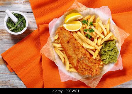 croustillants fish and chips - morue frite, frites de français, tranches de citron, sauce tartare et pois moelleux sur plaque sur papier sur une vieille table en bois au romarin dans mort - Image