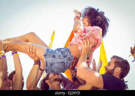 Happy hipster woman crowd surfing - Stock Image
