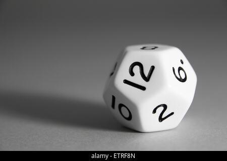 Un dodécaèdre noir et blanc ordinaire meurt avec douze visages et des chiffres sur un fond gris. - image d'archive