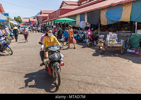 Femme warking masque masque équitation scooter à travers le marché, pakse, laos - Image