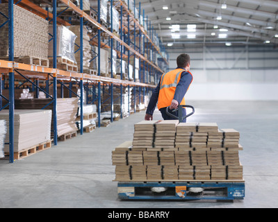 Worker Transporting Load In Warehouse - Stock Image
