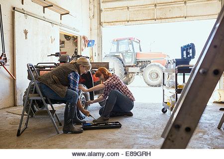 Mother and daughter repairing quadbike wheel - Stock Image