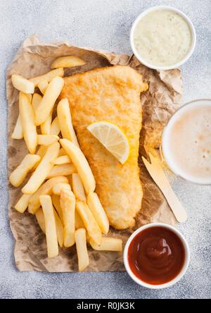 Fish and Chips britannique traditionnel avec sauce tartare abd verre de bière lager artisanale et ketchup à la tomate sur la planche sur une table en pierre blanche backgroun - Image