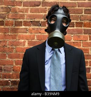 Homme d'affaires, debout à côté du mur de briques avec masque à gaz - Image
