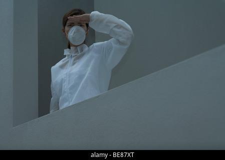 Femme au masque de pollution et combinaison de protection à la recherche, ombrageant les yeux - Image