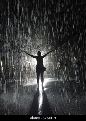 Woman standing in rain room - Stock Image