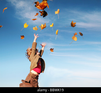 girl catching leaves in autumn - Stock Image