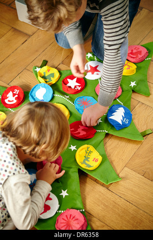 Children decorating Advent calendar, Munich, Bavaria, Germany - Stock Image