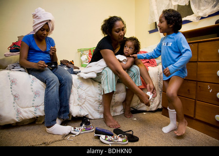 Selena Pina, a homeless mother of four, gets her children dressed for school at the Family Promises Center in Sacramento, - Stock Image