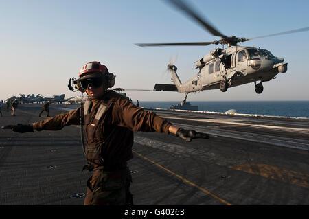 Airman checks for a clear deck as an MH-60S Sea Hawk takes off USS John C. Stennis. - Stock Image