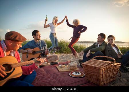Six amis adultes, faire la fête et danser sur la plage de Bournemouth, Dorset, Royaume-Uni - Image