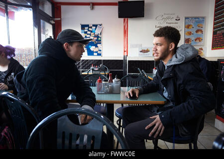 Two Male Students Eating Meal In Café - Stock Image