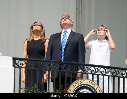 United States President Donald J. Trump, center, accompanied by first lady Melania Trump, left, and Barron Trump, right, look at the partial eclipse of the sun from the Blue Room Balcony of the White House in Washington, DC on Monday, August 21, 2017. Credit: Ron Sachs / CNP   - NO WIRE SERVICE - Photo: Ron Sachs/Consolidated/dpa - Stock Image