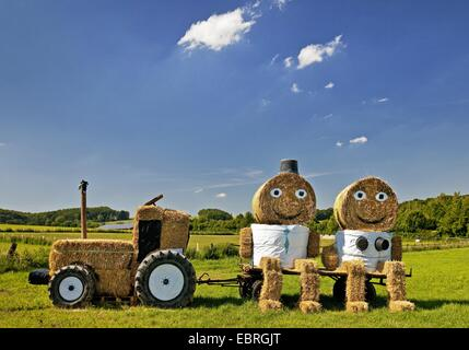 tractor and a couple made of bales of straw, Germany, North Rhine-Westphalia, Coesfeld - Stock Image