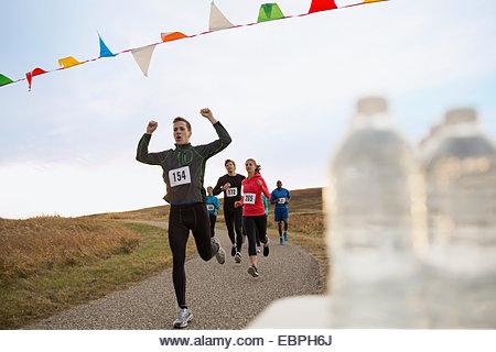 Cheering runner approaching finish line - Stock Image