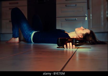 Jeune femme allongée sur le sol de la cuisine avec une bouteille de bière - Image
