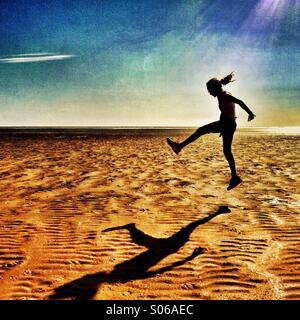 Girl jumping on empty beach - Stock Image