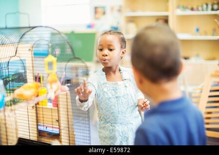 Students examining birdcage in classroom - Stock Image