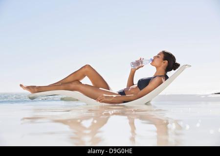 Beautiful woman drinking water on the beach - Stock Image