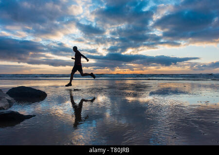 Seaton Carew, County Durham, UK. 10th May 2019. UK Weather: A glorious sunrise on a chilly Friday morning as a jogger runs along the beach at Seaton Carew on the north east coast of England. Credit: Alan Dawson/Alamy Live News - Stock Image