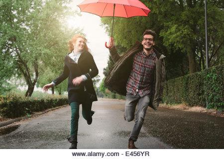 Couple running in park under umbrella - Stock Image