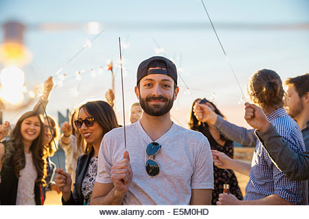 Portrait of smiling man with sparkler at party - Stock Image