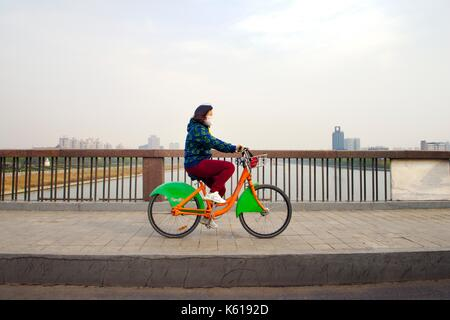 Ville de Taiyuan, Shanxi, Chine. Jeune femme portant le masque de pollution de l'air manèges ville communauté vélo part cycle sur la rivière Fen - Image