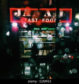 Fast food restaurant takeaway on a rainy night - Stock Image