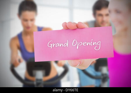 Fit blonde holding card saying grand opening - Stock Image
