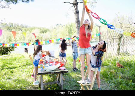Young woman hanging up bunting - Stock Image