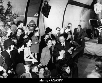 GEORGE FORMBY UK music-hall artist entertains Londoners sheltering from German bombing in  Aldwych underground station - Stock Image