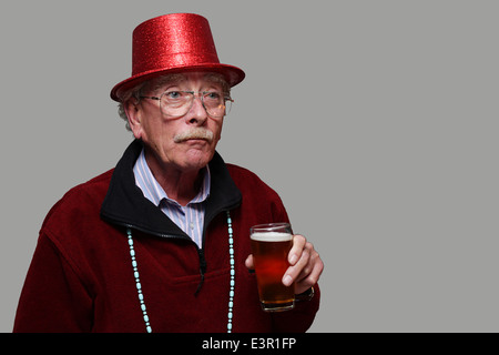 Un vieil homme dans un chapeau de fête rouge tenant un verre de bière - Image