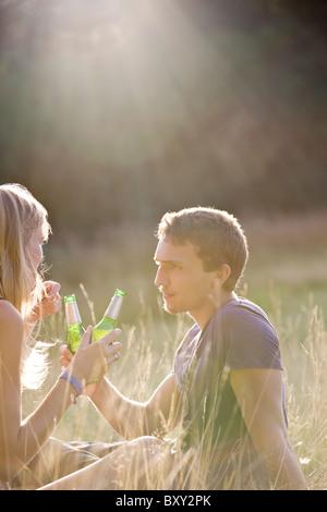 Un jeune couple assis à l'extérieur sous le soleil du soir, boire de la bière - Image