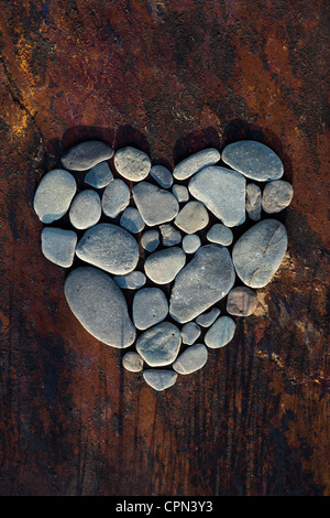 Heart shape pebbles on a texture slate background - Stock Image