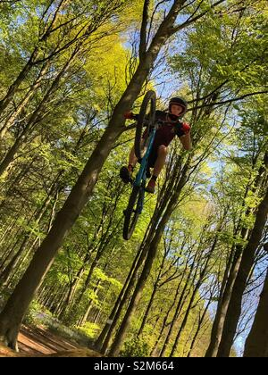Mountain biker getting big air over a jump in the forest - Stock Image