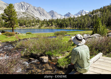 Resting hiker admires view in Little Lakes Valley in Rock Creek Canyon in the Eastern Sierra in Northern California - Stock Image