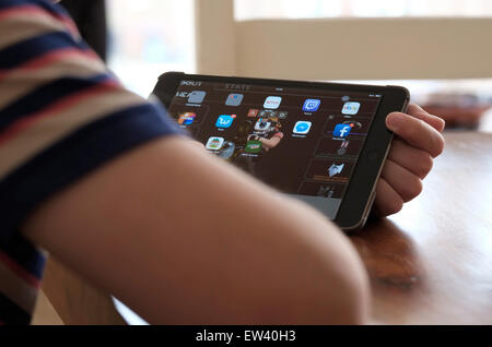 young male boy using ipad mini tablet computer - Stock Image