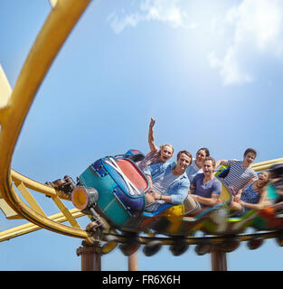 Cheering friends riding roller coaster at amusement park - Stock Image